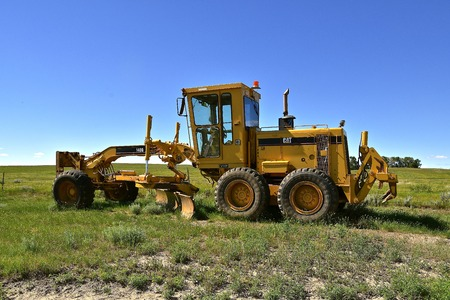 ISABEL, SOUTH DAKOTA, June 23, 2017: The old road grader parker in a pasture is a product of Caterpillar, INC, the world's leading manufacturer of construction and mining equipment, diesel and natural gas engines, industrial gas turbines and diesel-electr