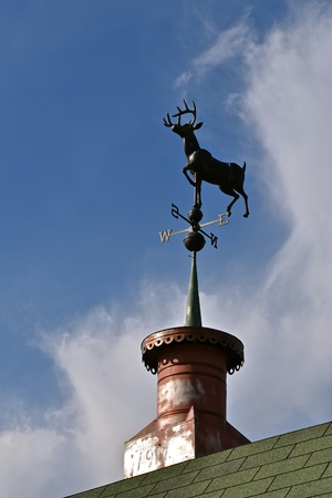 Foto de A wind vane with a running buck deer anchored to a cupola is silhouetted n the sky - Imagen libre de derechos