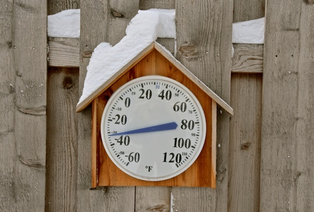 A snow covered thermometer records a chilly negative 32 degrees Fahrenheit.