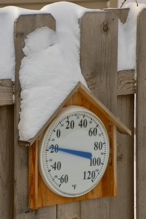A thermometer surrounded by snow after a wintry snowstorm reads -16 degrees below zero