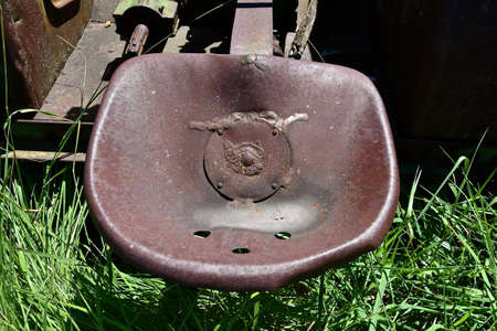 Photo pour An old tractor seat is full of rust and has holes holes rain drainage. - image libre de droit