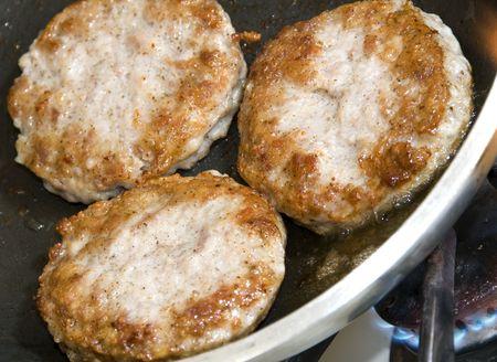 pork sausage patties cooking in frying pan
