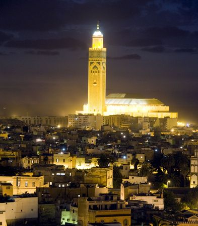 Hassan II mosque night scene at dusk sundown with lights overlooking the Atlantic Ocean in Casablanca Morocco Africa which is the largest mosque in Morocco and the third largest mosque in the world