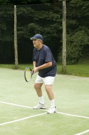 overweight senior man actively playing tennis on private club tennis court