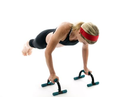 attractive middle age female fitness trainer exercising with fitness push up bars