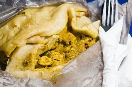 dahl pouri roti  trinidad native food wrap also called bust up shot or dosti roti fast food with curried chicken pumpkin  potatoes and ground chick peas