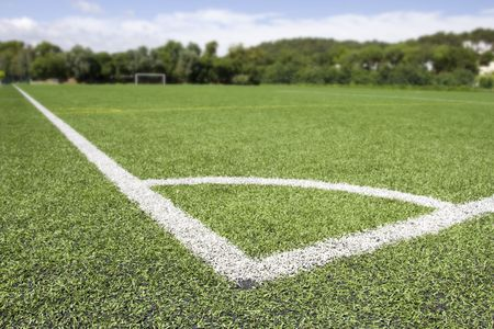 Green grass and corner lines of an outdoor football field (artificial covering)