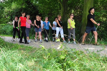 Munich, Germany - July 21, 2009: People doing nordic walking with coaches sponsored by german health insurances to support active living