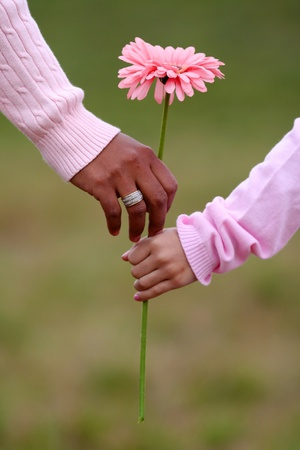 Photo for Mother and daughter holding a flower while walking together - Royalty Free Image
