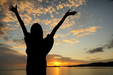 Girl raising her hands during sunset at the beach