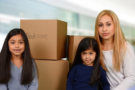 Mother and her two young daughters packed moving boxes