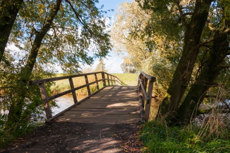 Wooden bridge over a small river in a rural autumn landscape