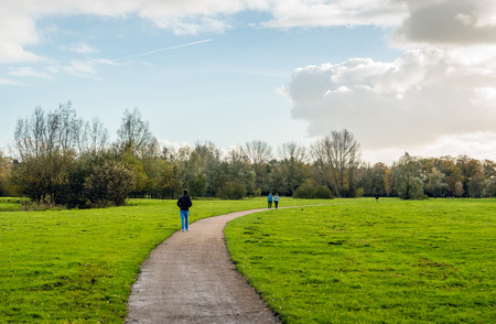 One man and two women walking in an autumnal Dutch rural landscape on a cloudy day in the fall season.