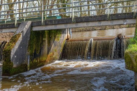 Photo pour Water in a narrow Dutch river flows over the weir under the bridge. There is a water level meter on both sides of the weir on the wall. - image libre de droit