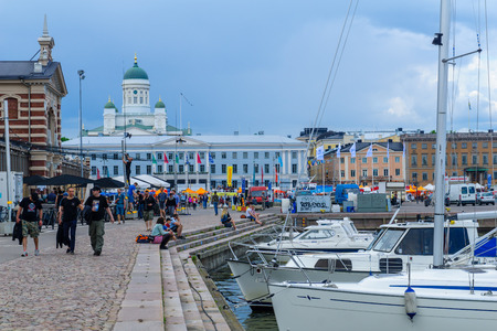 HELSINKI, FINLAND - JUNE 15, 2017: Scene of the south harbor, with the market, the city hall, the Lutheran Cathedral in the background, locals and visitors, in Helsinki, Finland