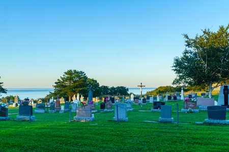 Grosses-Roches, Canada - September 12, 2018: The cemetery of the Les Saints-Sept-Freres Catholic church, in Grosses-Roches, Gaspe Peninsula, Quebec, Canada