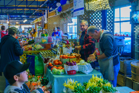 Quebec City, Canada - September 27, 2018: Scene of old port market, with fruits and vegetables, sellers and shoppers, in Quebec City, Quebec, Canada