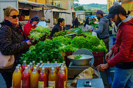 Le-Bois-de-Oingt, France - May 07, 2019: French market scene with sellers and shoppers in Le-Bois-de-Oingt, Beaujolais, Rhone department, France