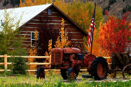 Rusty tractor sits in autumn color with U.S. flag