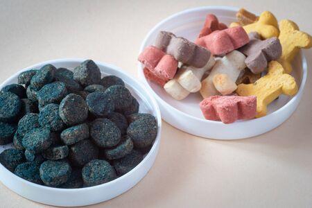 Foto de Dog treats and spirulina for pets, in small bowls, pale background. Training & healthy animals. - Imagen libre de derechos