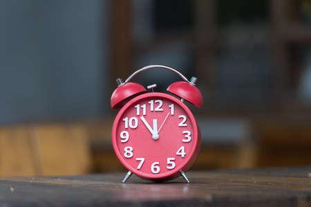 Retro alarm clock with five minutes to twelve o\'clock.