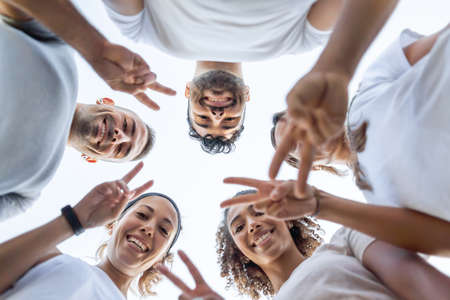 Photo pour Group of young beautiful friends looking down at the camera showing fingers v-sign - Low angle view of five cute people doing victory sign together - image libre de droit
