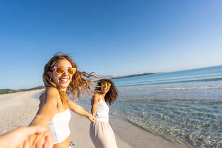 Photo pour Two young beautiful girls with colorful sunglasses dress boho in summer looking at camera on the beach laughing amused for happiness on vacation pulling hand of the photographer in follow me gesture - image libre de droit