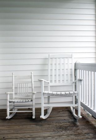 An adult's and child's rocking chairs on a front porch.