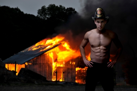 Young attractive male firefighter at a fire