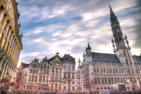 Wide angle night scene of the Grand Place, the focal point of Brussels, Belgium. The Town Hall (Hotel de Ville) is dominating the composition with its 96m tall spire