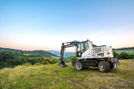 Photo pour Volovets, Ukraine - 08/27/2020: HIDROMEK 140w excavators on a background of mountains and forests. - image libre de droit