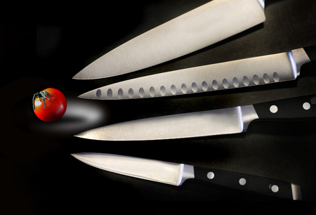 Assorted sharp and shiny kitchen knives are seen with a small tomato in this photograph.