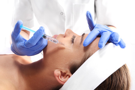 Photo pour Portrait of a white woman during surgery filling facial wrinkles, Cosmetic is injected into facial skin cosmetics - image libre de droit