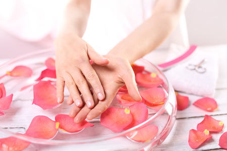 Smooth leather palm beauty treatment clinic.Treatment hand and nail care women hold hands vial of rose oil over the bowl with rose petalsの写真素材