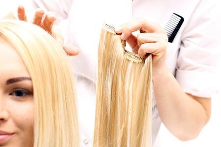 Photo pour Hair extensions. Barber prolongs the hair strands of hair buttoning - image libre de droit