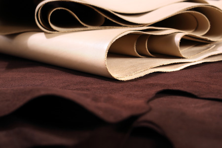 Photo pour Grain leather. The composition of brown and vanilla leather and shoe accessories - image libre de droit