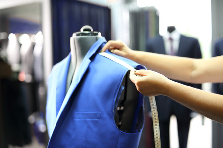 Foto de Men seamstress, a suit made to measure. The production plant, sewing jackets for seamstress - Imagen libre de derechos