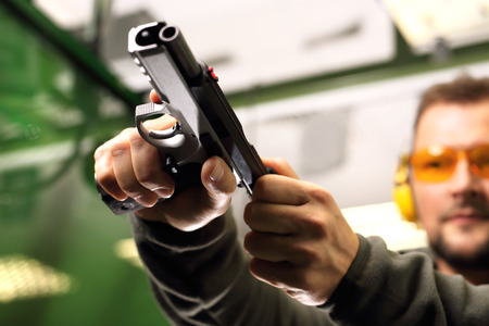 Shooting range. The man at the pistol shooting reloads