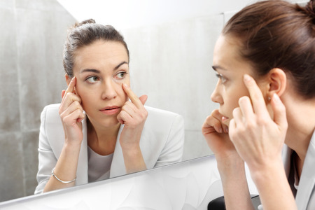 Foto de Reflection in the mirror. Woman looks in the mirror noticing the first wrinkles - Imagen libre de derechos