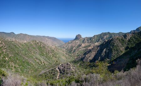 The elongated valley of Vallehermoso, La Gomera, Canary Islands, Spain, northbound. In the middle the distinctive rock summit Roque El Cano.