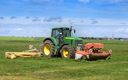 Foto für Traktor mäht Gras auf einem Feld  Tractor mowing grass on a field - Lizenzfreies Bild