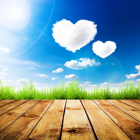 Photo pour Green grass on wooden plank over a blue sky with hearts shape clouds. Beauty natural background - image libre de droit
