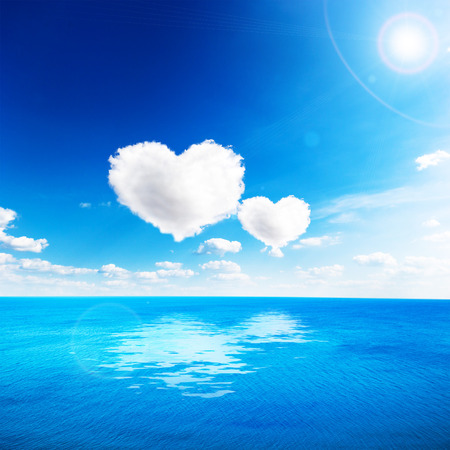 Foto de Blue sea under clouds sky with heart shape cloud. Valentine background - Imagen libre de derechos
