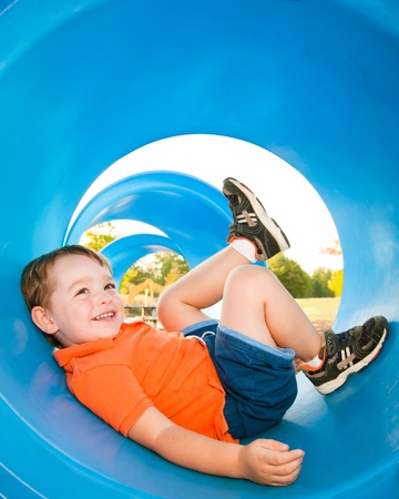 Photo pour Cute young boy playing in tunnel on playground.  - image libre de droit