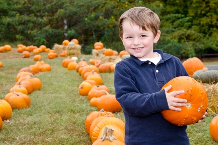 Foto de Happy young boy picking a pumpkin for Halloween  - Imagen libre de derechos