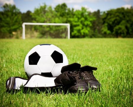Photo pour Child sports concept with soccer ball, cleats, shin guards on field - image libre de droit