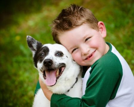 Photo pour Child lovingly embraces his pet dog, a blue heeler - image libre de droit