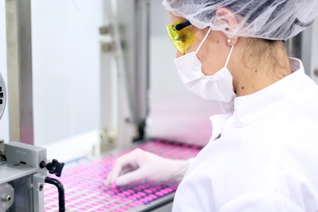 Technician inspecting the quality of pills at a pharmaceutical plant.
