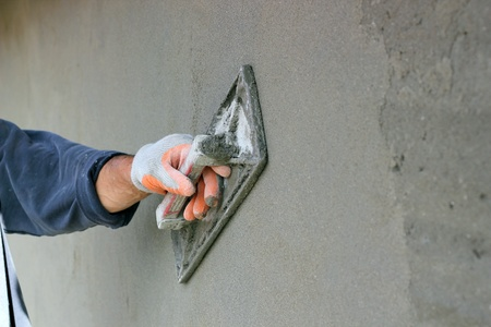 Man s hand plastering a wall with trowel  Selective focus