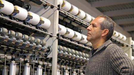 Photo pour Engineer Examining Thread in Textile Mill - image libre de droit